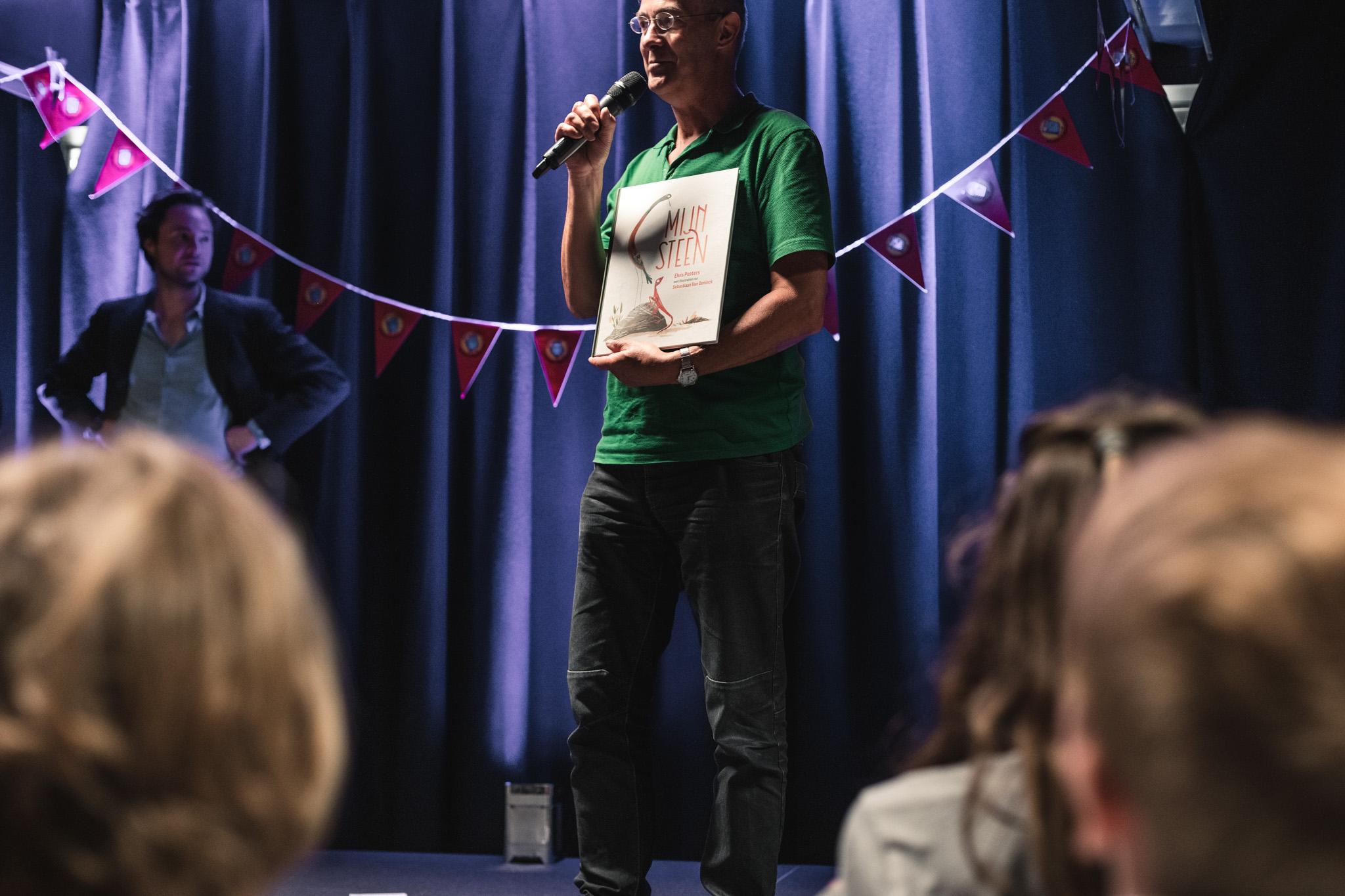 jeugdauteur elvis peeters leest voor op het podium tijdens een slotfeest van de kinder- en jeugdjury