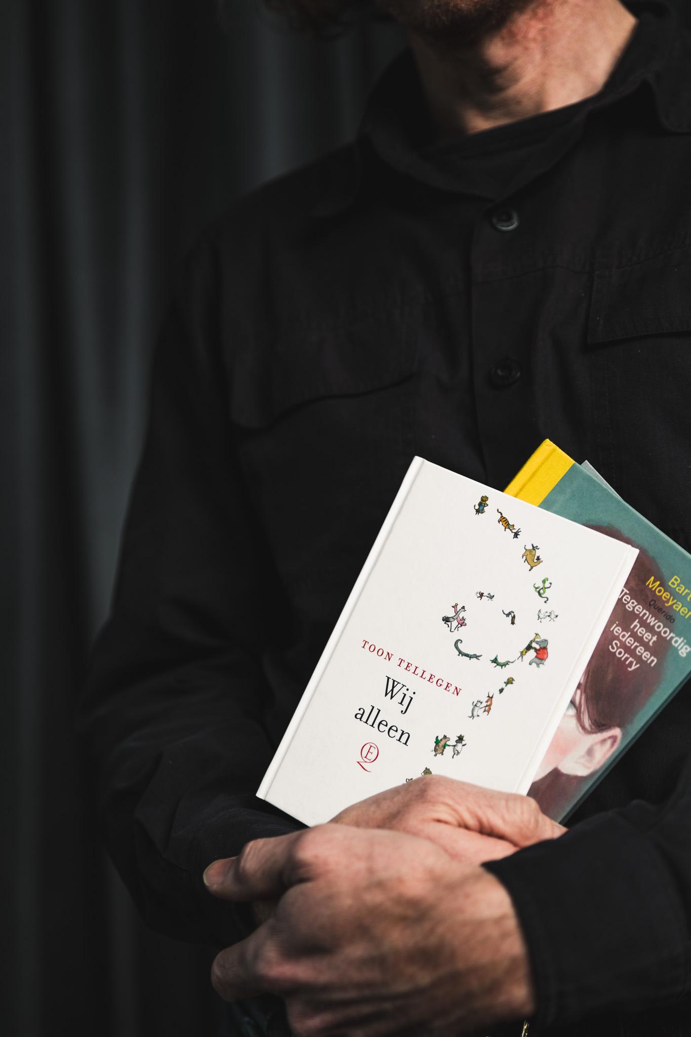 Hendrik Vos, niet met gezicht in beeld, houdt twee jeugdboeken vast: Wij Alleen van Toon Tellegen en Tegenwoordig heet iedereen Sorry van Bart Moeyaert