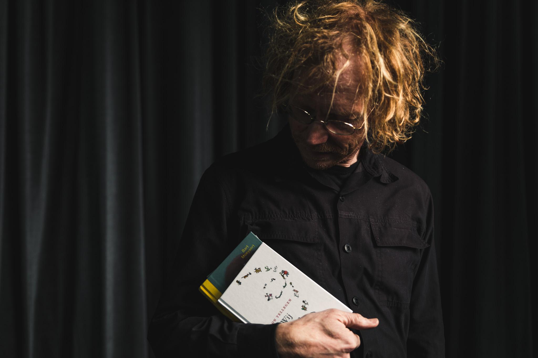 portret van Hendrik Vos, die twee boeken in zijn rechterarm vasthoudt. Hij kijkt naar de boeken. Op de achtergrond hangt een donkergrijs fluwelen gordijn.