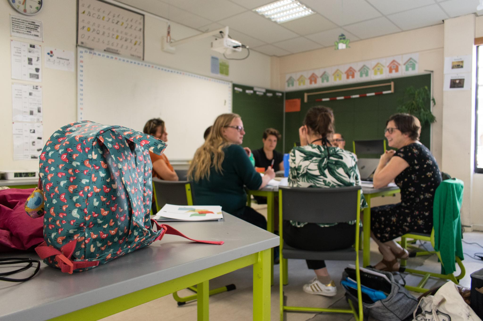 Leerkrachten zitten in een klas samen aan tafel en wisselen ideeën uit. Op de voorgrond staat een schooltas van een kind.