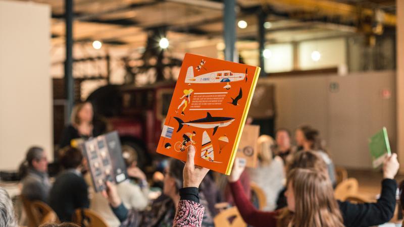 tijdens een workshop steekt een deelnemer een non-fictie boek in de lucht
