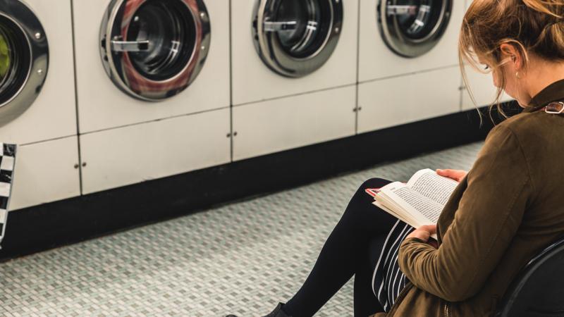 een vrouw leest een boek in een wassalon.