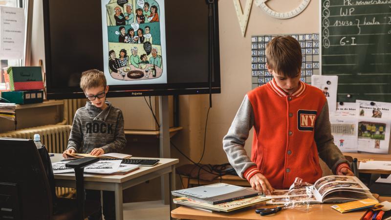 Leerlingen snuisteren in boeken in de klas