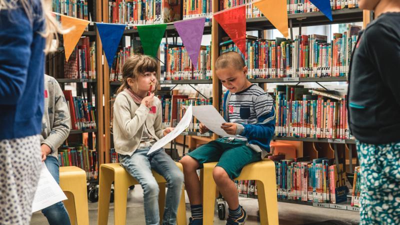 Kinderen nemen deel aan een boekenzoektocht in de bibliotheek