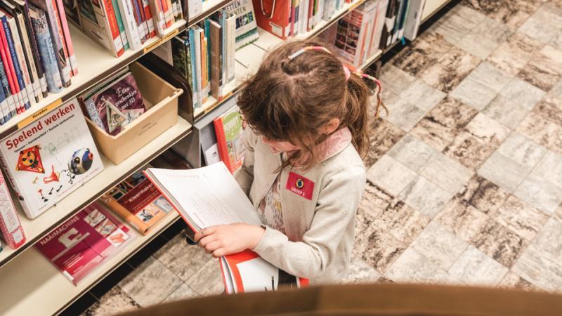 Meisje kiest een boek uit een boekenkast