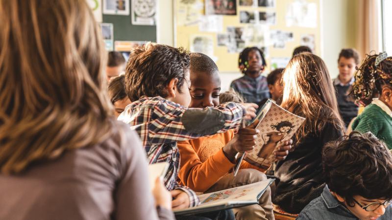 Kinderen lezen samen in de klas