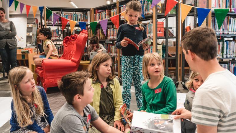 kinderen luisteren naar auteur in de bibliotheek