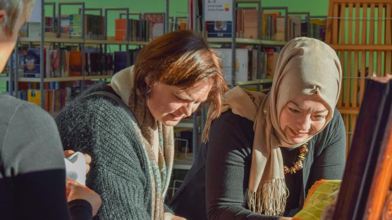 bezoekers bekijken een tentoonstelling in de bibliotheek