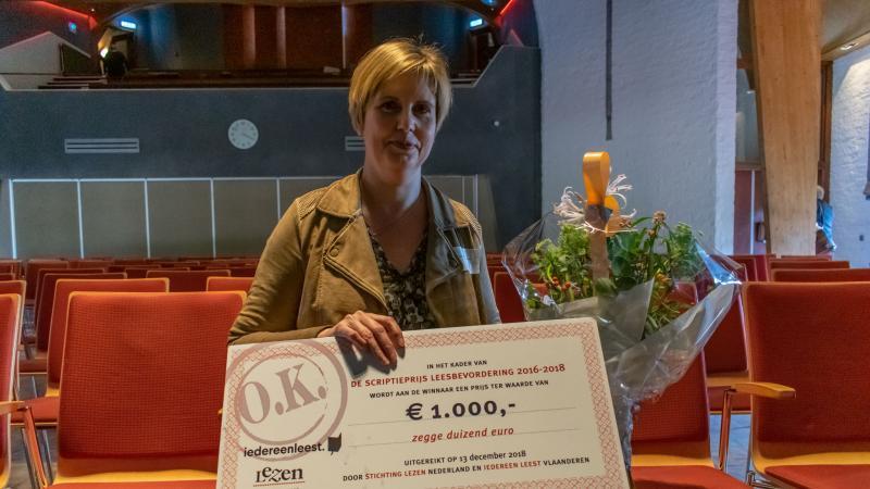 Winnaar van de Scriptieprijs Leesbevordering met bloemen en cheque