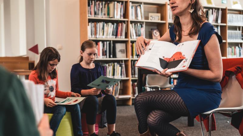 kinderen in bibliotheek luisteren naar iemand die een prentenboek voorleest