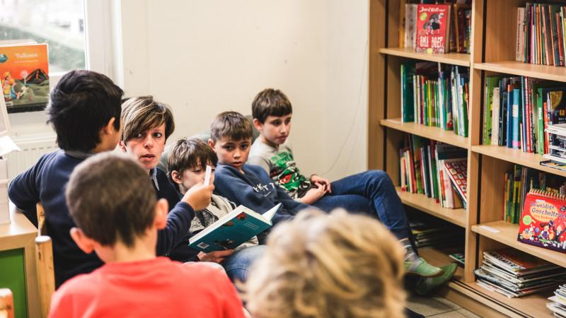Leerlingen zitten op een rij. In het midden leest een juf voor. Rechts staat een boekenkast