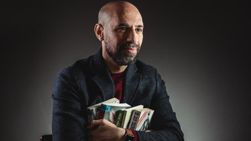 Portret van auteur Abdelkader Benali. Hij omklemt vier boeken in zijn armen en kijkt weg van de lens. De achtergrond is grijs.