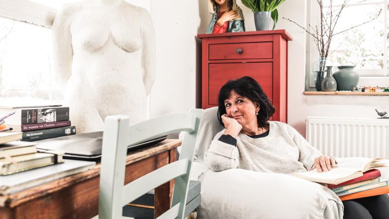 Auteur Kristien Dieltiens zit rechts in de zetel met boeken op haar schoot. Links liggen op tafel haar favoriete boeken.