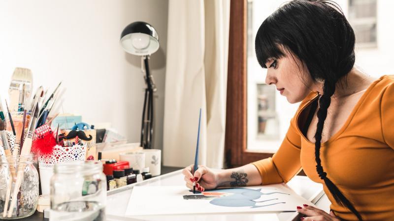 Illustrator Fatinha Ramos zit aan de tekentafel. Voor haar ligt een blad papier met een half afgewerkte illustratie, die ze met haar rechterhand verder afwerkt.