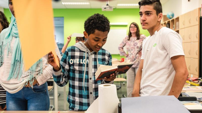 twee jongeren kijken in een boek tijdens een workshop in de klas met een jeugdauteur