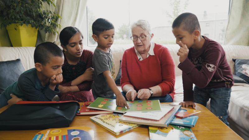 Vier kinderen zitten aan de salontafel, een vrijwilligster leest voor. Op de salontafel liggen verschillende prentenboeken.
