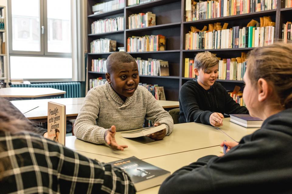 Leerlingen praten over boeken in een schoolbibliotheek