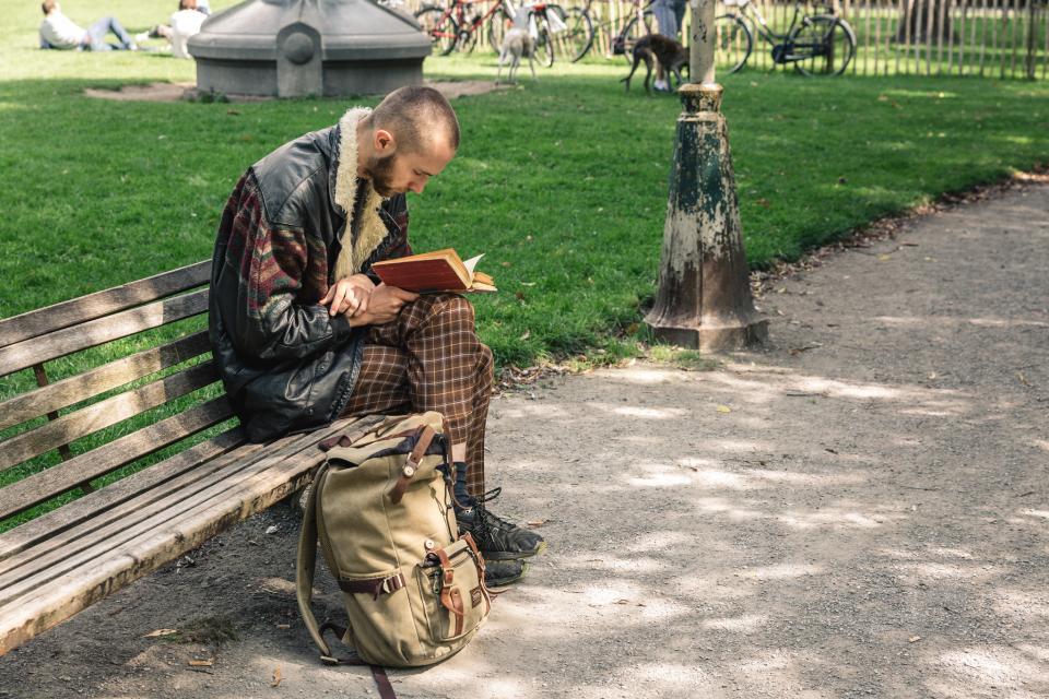 man leest boek op een bank in het park