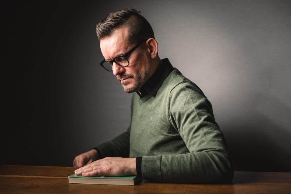 Jeugdauteur Bart Moeyaert zit aan tafel. Daar ligt een boek waarop zijn linkerhand rust. De achtergrond is effen grijs.