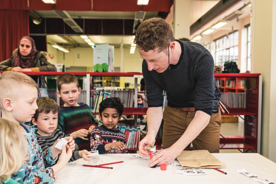 kinderen knutselen een eigen verhaal tijdens een workshop met een illustrator in de bibliotheek