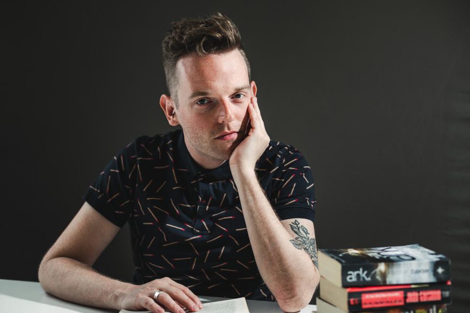 portret van tom de cock die aan tafel zit met boeken rondom hem. Zijn hoofd rust op zijn linkerhand, zijn rechterhand ligt op een opengeslagen boek. De achtergrond is donkergrijs.