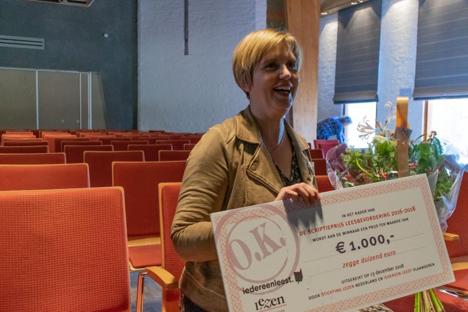 de vorige winnaar van de scriptieprijs leesbevordering houdt een cheque van €1000 in haar handen