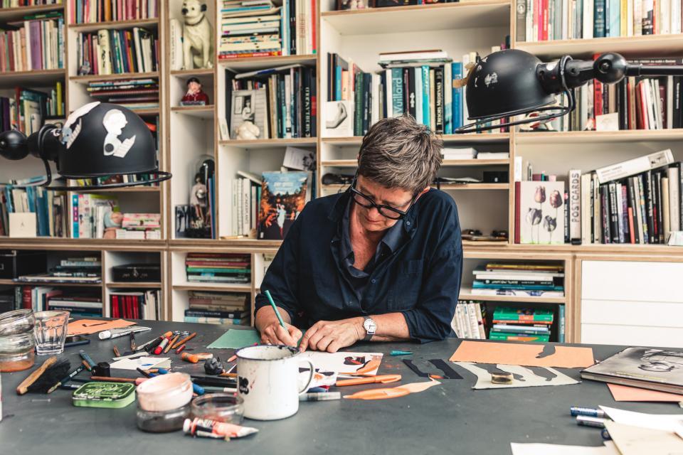 illustrator ingrid godon tekent op papier aan een bureau in haar atelier