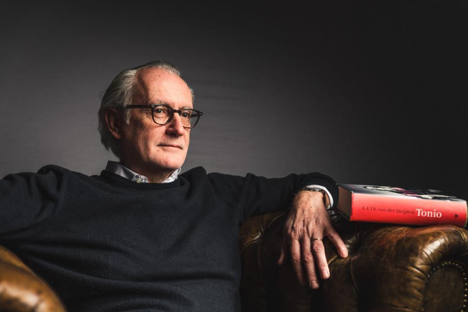 portret van Peter D'Hondt die in een lederen zetel zit. Rechts ligt het boek Tonio van van der Heijden op de armleuning.