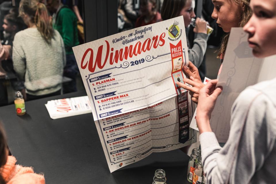 juryleden houden de affiche met de winnaars van de kinder- en jeugdjury vast
