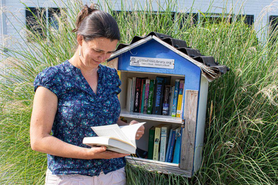 een eigenaar van een boekenruilkastje poseert naast haar kastje terwijl ze door een boek bladert