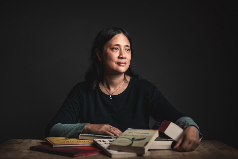 portret van winny ang die aan tafel zit. Voor haar liggen boeken verspreid op tafel. De achtergrond is donkergrijs.