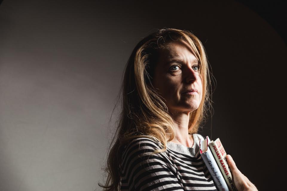 rika ponnet poseert voor de lens met haar favoriete boeken in haar armen. Ze kijkt weg van de lens. De achtergrond is effen, in grijs en zwart.