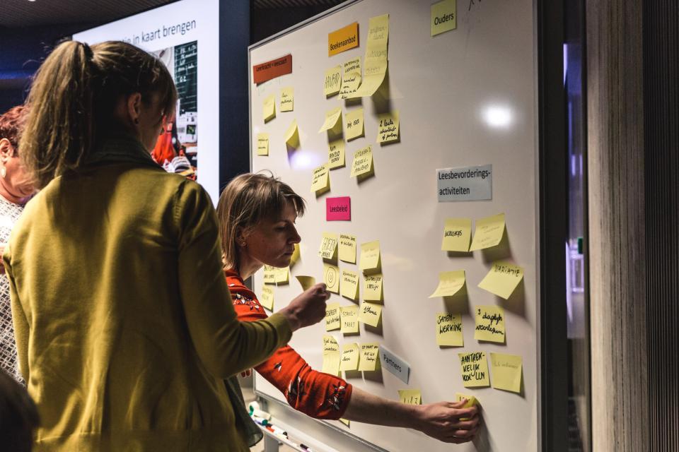 twee deelnemers aan een workshop kleven post-its op een flipchart