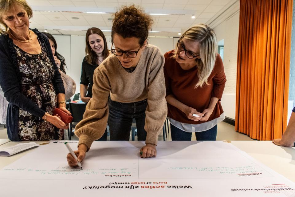 Bibmedewerkers schrijven acties rond meertaligheid neer op een groot blad tijdens een workshop in de bibliotheek.