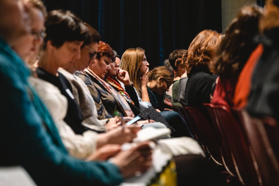 deelnemers van de conferentie zitten op stoelen in een zaal