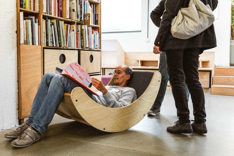 man zit een kinderboek te lezen in een houten schommelzetel - op de achtergrond staat een boekenkast