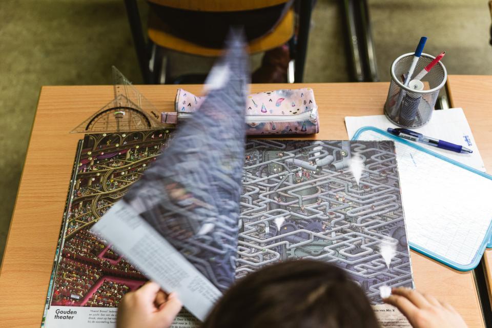 Een leerling slaat de bladzijde van een groot prentenboek om dat op een lessenaar ligt. De foto is genomen van bovenaf. Op de lessenaar liggen geodriehoeken, een etui, schrijfgerei en een schrift.