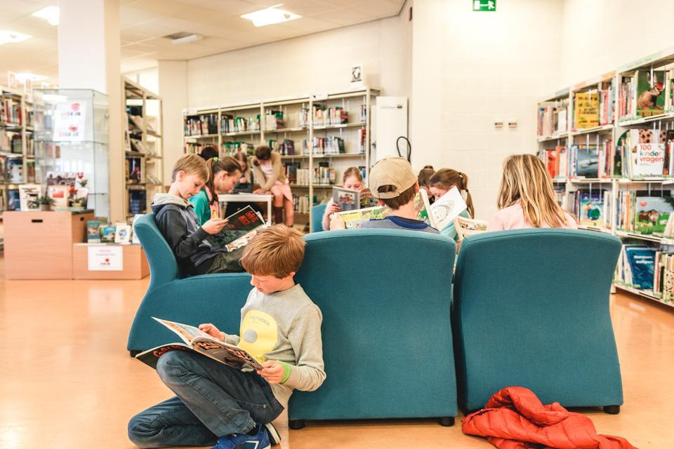 kinderen lezen al zittend strips in de bibliotheek