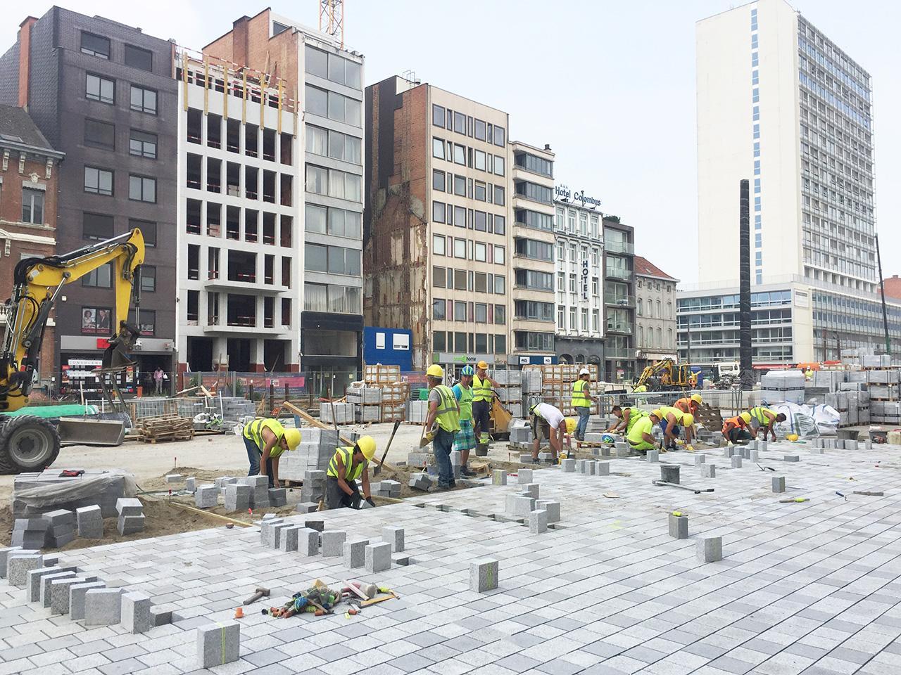 bouwvakkers leggen tegels aan het Operaplein