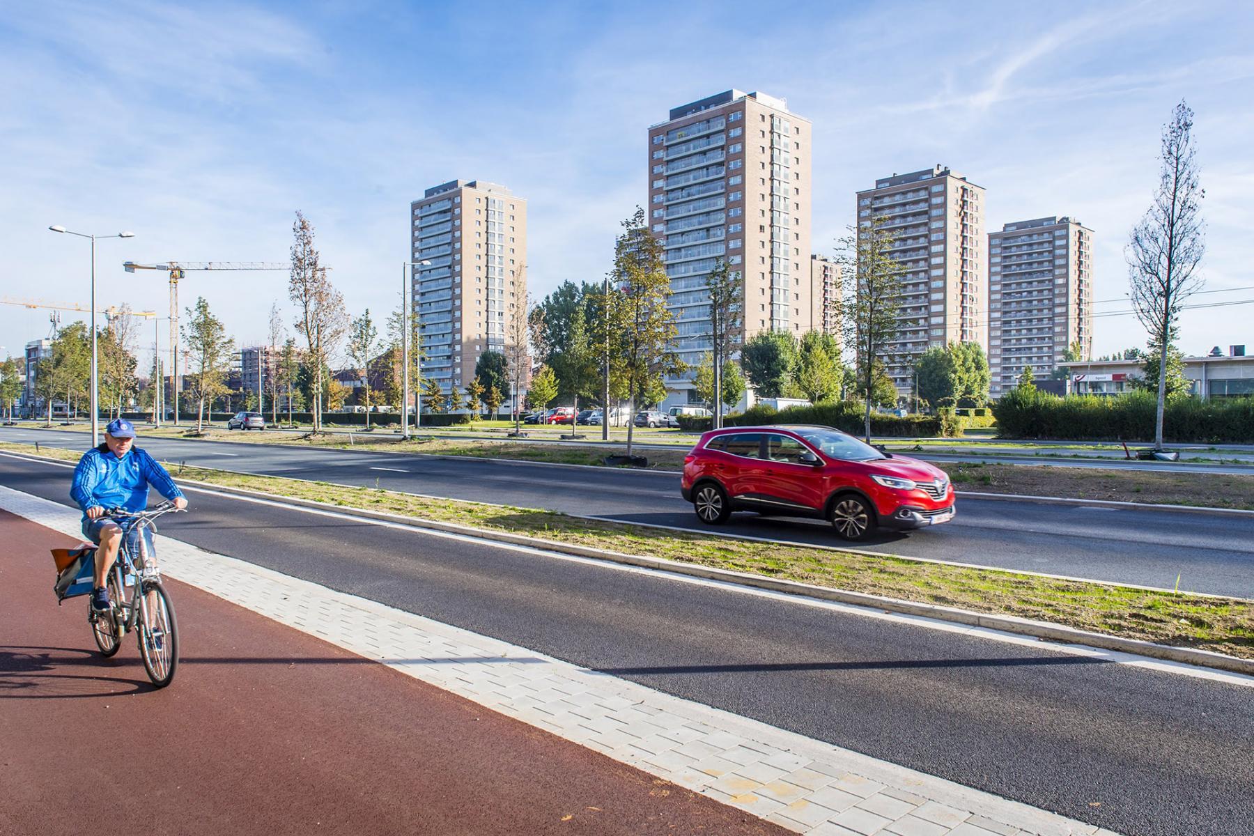 fietser op fietspad van nieuwe Noorderlaan met rode auto en hoogblokken op de achtergrond