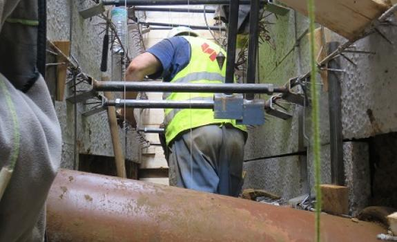 Foto van een man aan het werk in de smalle sleuf.