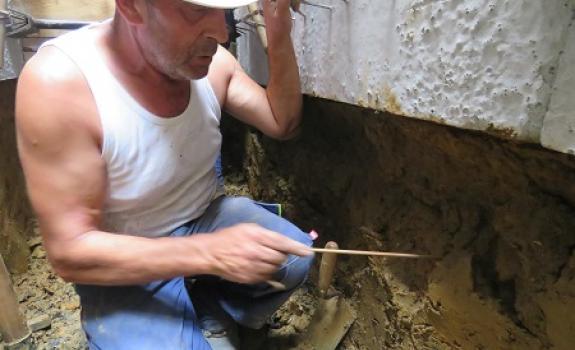 Foto van een man aan het werk in de sleuf.