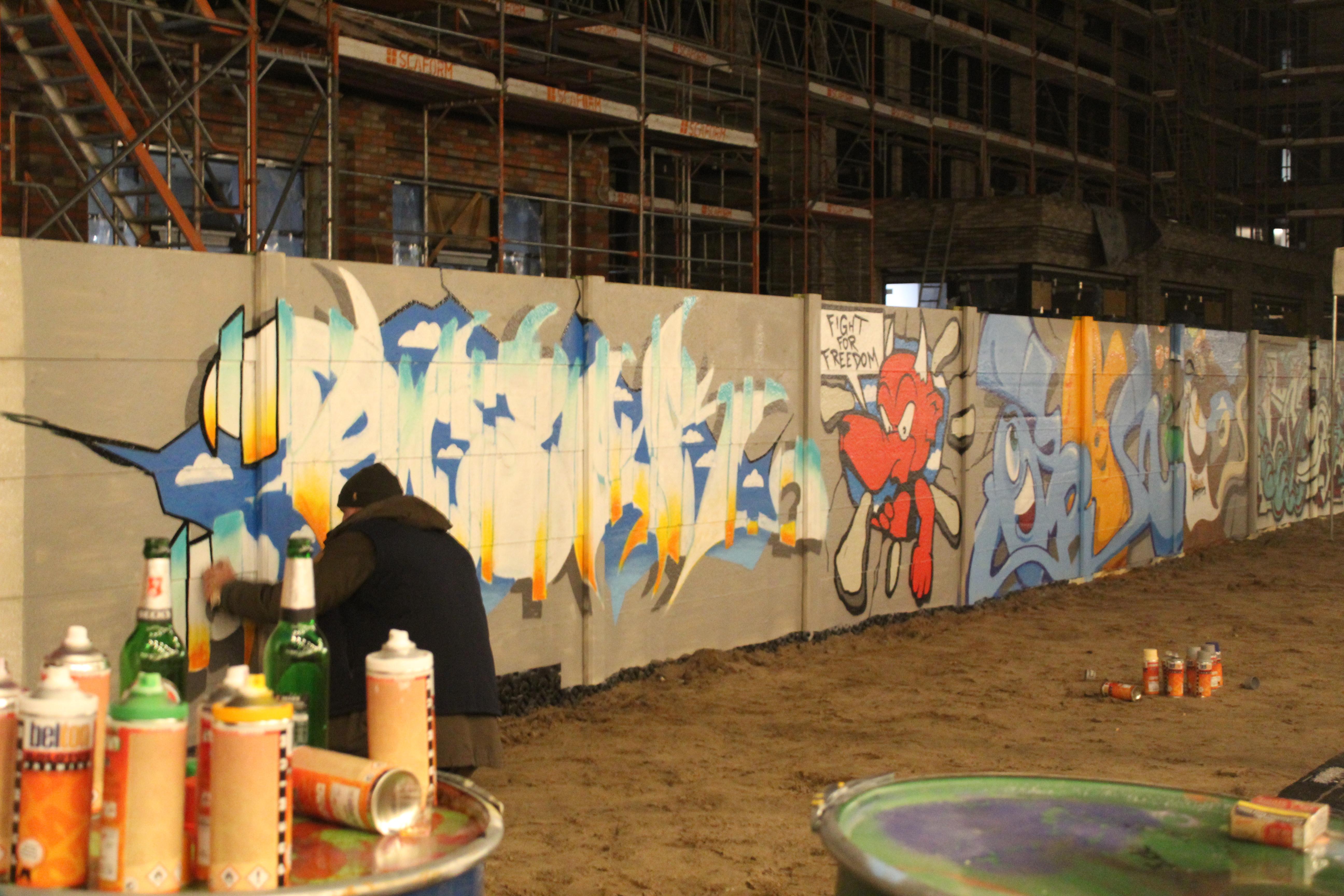 Grafitti artiesten bewerken een muur in Berlijn