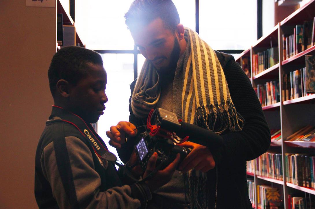 Anouar legt aan een jongen uit hoe hij een camera moet gebruiken