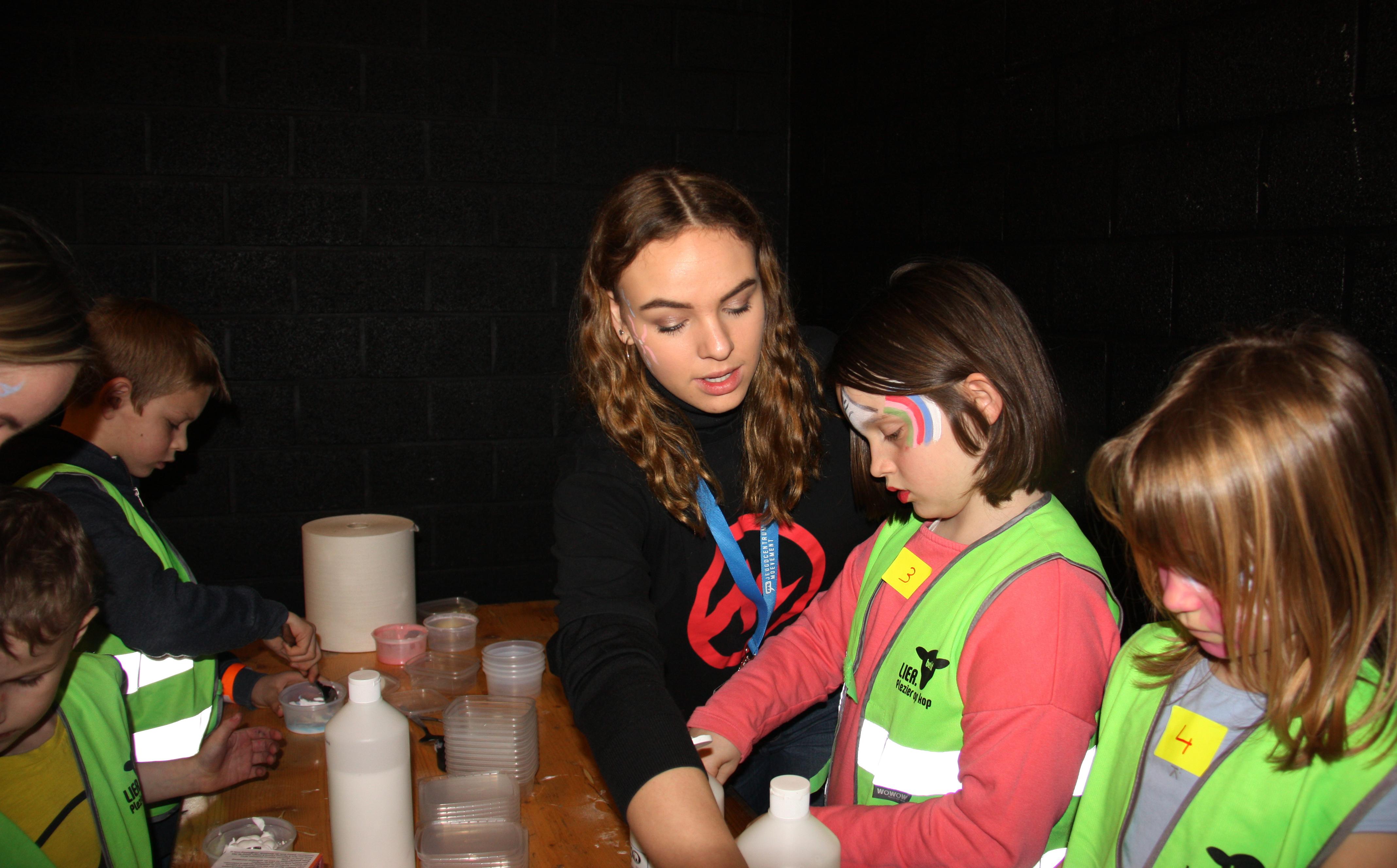 leerling helpt kinderen met knutselen