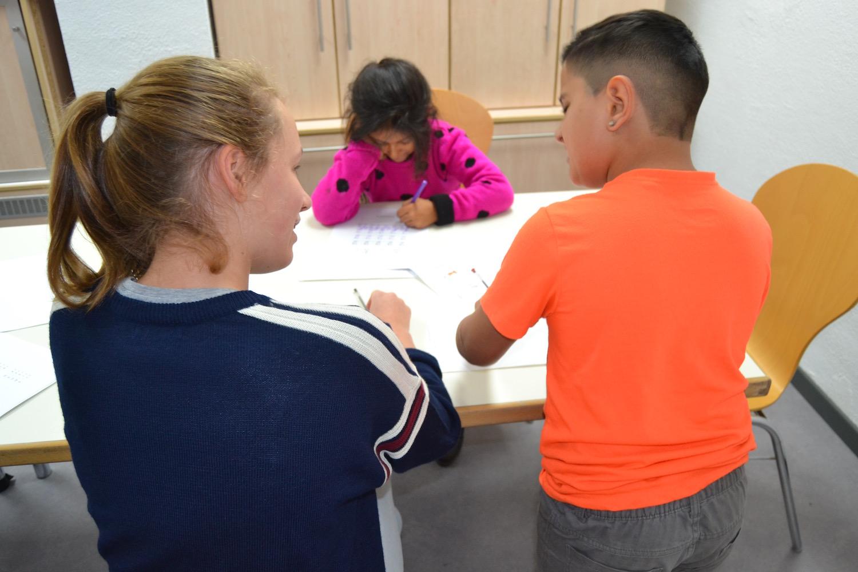 Een jongere helpt twee Romakinderen met hun huiswerk.