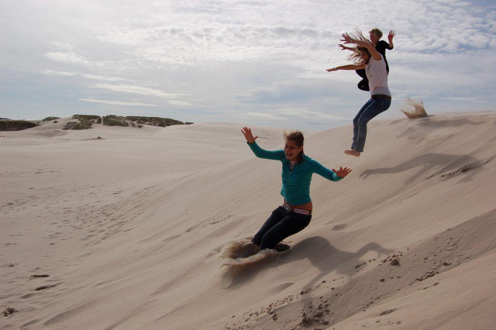 Jongeren springen van een zandduin
