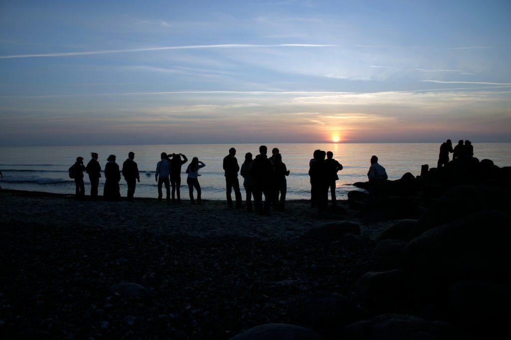 Jongeren op het strand bij zonsondergang