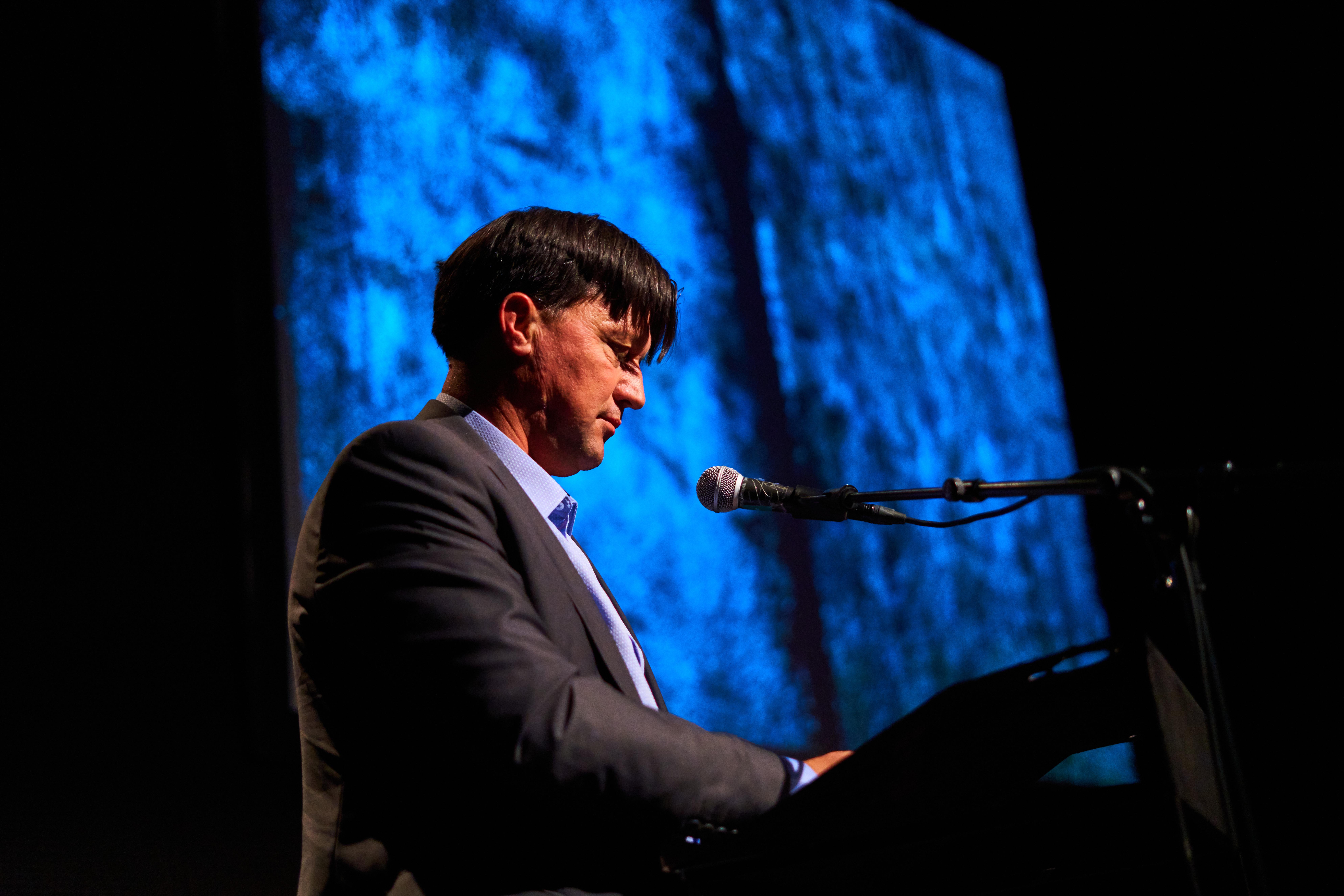 Man leest voor op podium met blauwe achtergrond