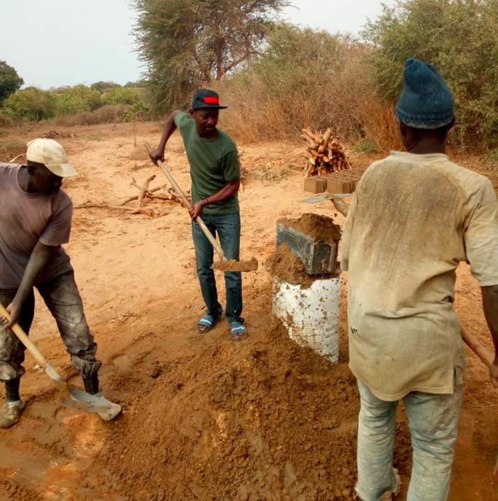 Senegalese arbeiders werken aan de bouw van een kippenkwekerij
